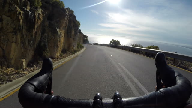 pov_pro female cyclist riding down mountain road with training partner - moving past stock-videos und b-roll-filmmaterial