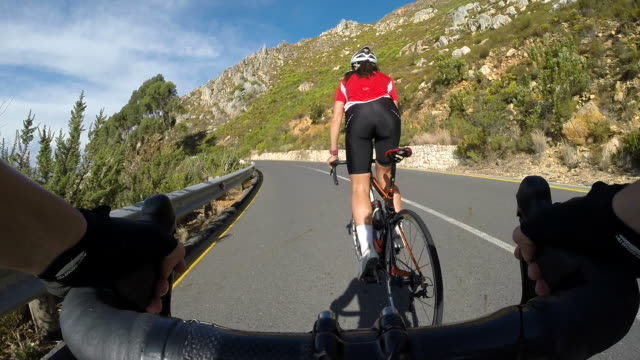POV_Two female cyclists riding up mountain road