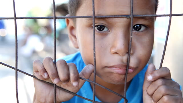 hd poverty - asian boy behind fence - looking around stock videos & royalty-free footage