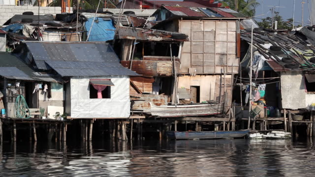 hd poverty housing along river - stilts stock videos and b-roll footage