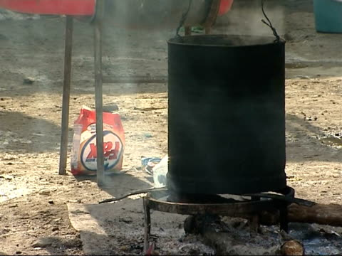 ext steam rising from pot containing boiling water sitting on an open fire in ground outside home in poor village / washing hanging on line / pot... - rumänien stock-videos und b-roll-filmmaterial