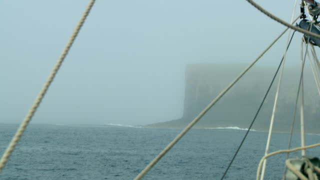 povs boat moves towards isle of staffa in mist, scotland - ominous stock videos & royalty-free footage
