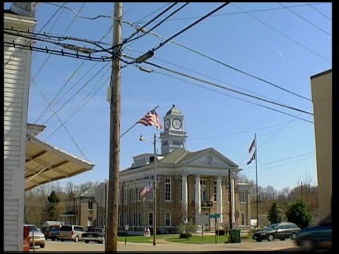 pow town itn usa west virginia elizabeth log truck along past town hall us flag flying at half mast tilt down smith towards yellow ribbons tied to... - channel 4 news stock videos and b-roll footage