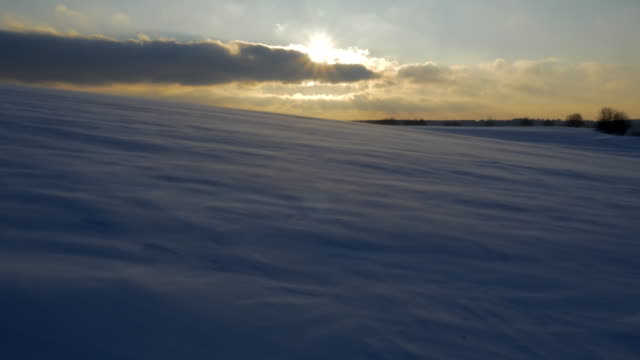 powder snow races down slanted open field with sun