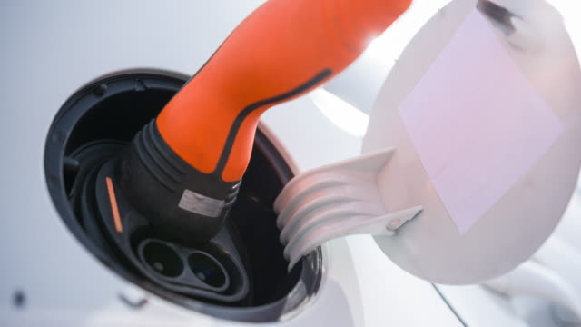 Power cable being plugged in electrical outlet of alternative fuel powered vehicle close up