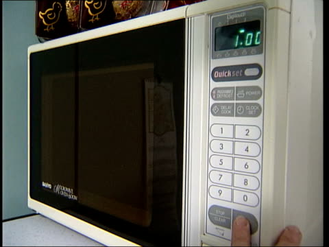 electricity companies failing to pass on price cuts news at ten penny marshall microwave oven as hand pressing buttons to start cooking kettle as... - microwave stock videos & royalty-free footage