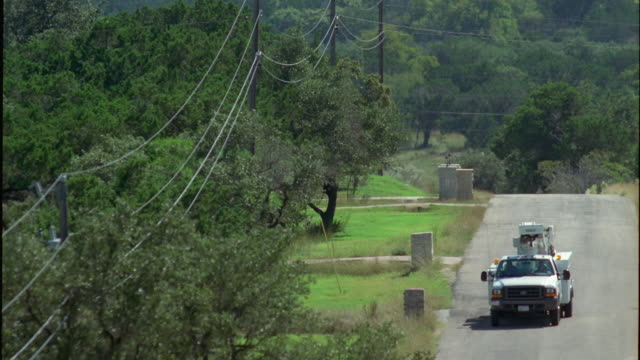 slo mo ws ha pan power lines above trees and truck driving down rural road / johnson city, texas, usa - johnson city texas stock videos & royalty-free footage