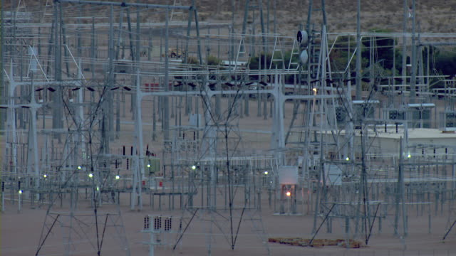 Power lines are suspended by utility towers at an electrical substation.