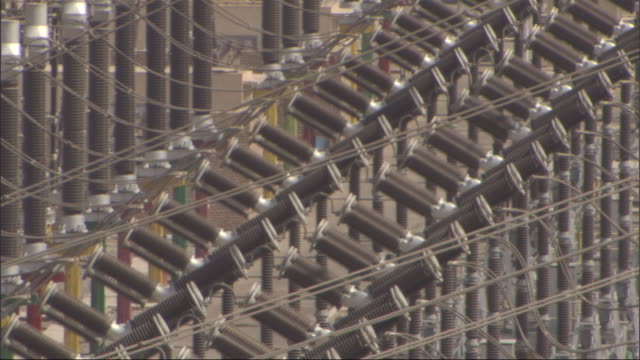 power lines criss-cross above a power station. - kraftwerk stock-videos und b-roll-filmmaterial