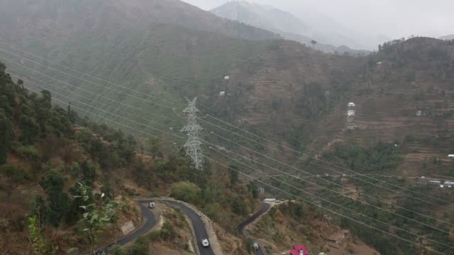 Power lines hang from a Sterlite Power Transmission Ltd transmission tower above a winding mountain road in Rajouri district Jammu and Kashmir India...