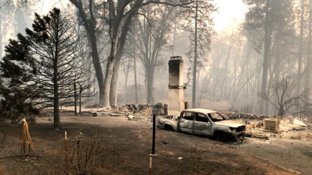 power lines rest on cars that were burned by the camp fire on november 10 2018 in paradise california - evacuazione video stock e b–roll