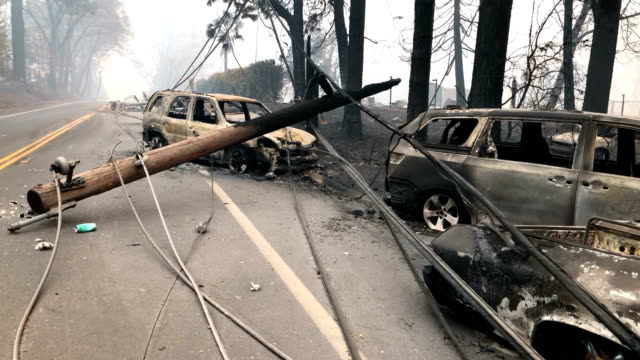 power lines rest on cars that were burned by the camp fire on november 10, 2018 in paradise, california. - 無加工 個影片檔及 b 捲影像