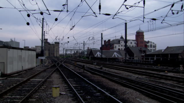 power lines run above railway tracks at newcastle east junction. available in hd. - railway junction stock videos & royalty-free footage