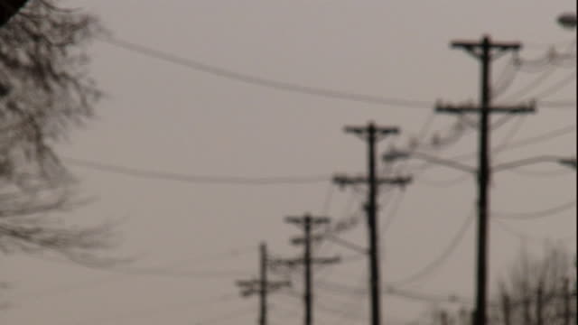 power lines sag between utility poles on an overcast day. - power line点の映像素材/bロール