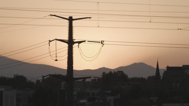 power lines silhouetted during sunset in denver - ケーブル線点の映像素材/bロール