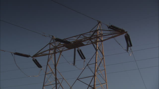 power lines stretch between electricity pylons. - transformer stock videos & royalty-free footage
