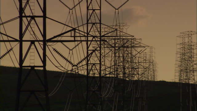power lines stretch from transmission towers. - sendeturm stock-videos und b-roll-filmmaterial