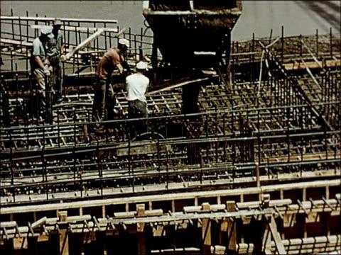 vidéos et rushes de power plant construction materials, concrete ingredients traveling up conveyor belt into mixer, male worker operating mixer controls, concrete being... - béton