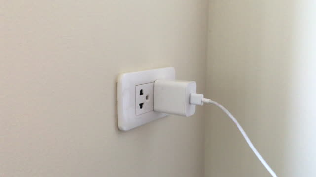 power plug adapter out women hand. - plugging in stock videos & royalty-free footage