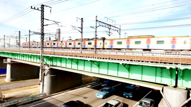 power railway with moving train over busy highway near seoul in blue sky