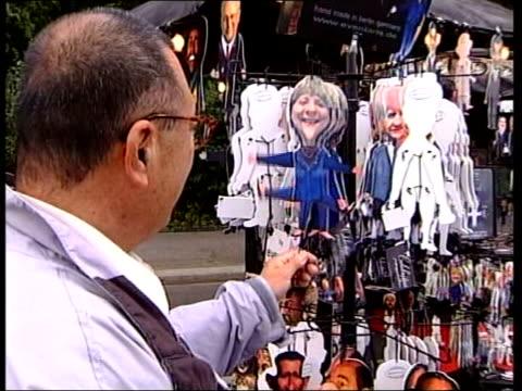 vídeos de stock e filmes b-roll de merkel becomes chancellor tx stall selling election souvenirs and caricatures of schroeder and merkel frankfurt int merkel into car at motor show... - democracia
