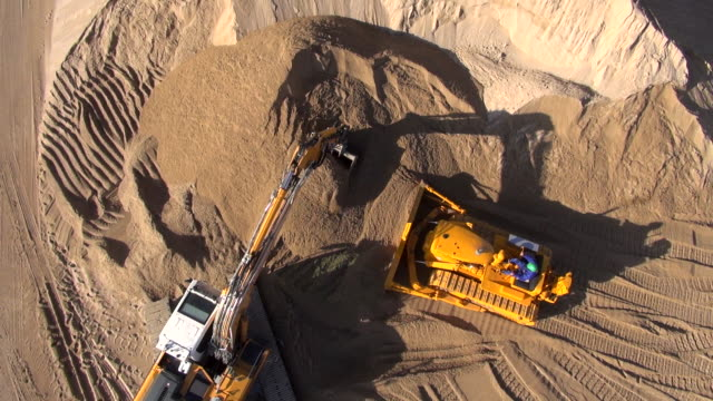A power shovel and bulldozer move material in a gravel pit.
