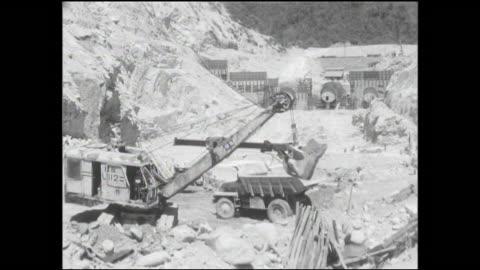 stockvideo's en b-roll-footage met a power shovel loads a dump truck at the yagisawa dam construction site. - dam mens gemaakte bouwwerken