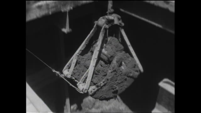 A power shovel removes dirt from a subway excavation and loads the dirt into a dump truck.