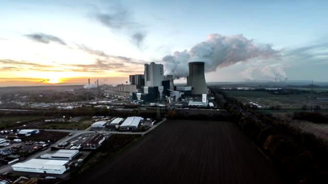 luftaufnahme: kraftwerk im sonnenuntergang - kraftwerk stock-videos und b-roll-filmmaterial