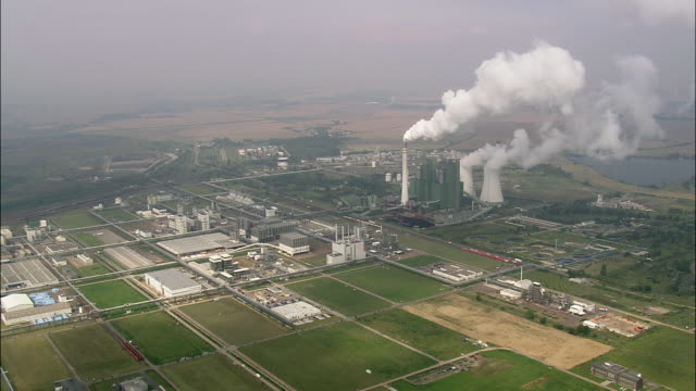 aerial power station emitting smoke through smoke stacks, schkopau, saxony, germany - smog stock-videos und b-roll-filmmaterial