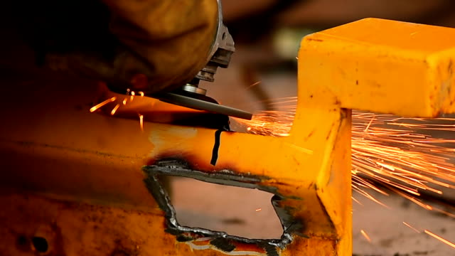 Power tool spitting sparks as it grinds a metal edge into shape