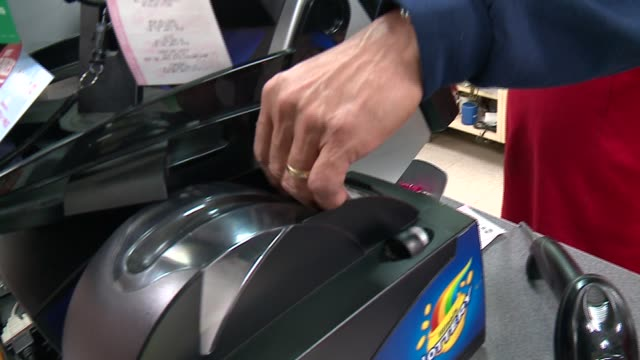 stockvideo's en b-roll-footage met powerball lottery ticket prints out of machine in a chicago convenience store on january 13, 2016 before the highest prize in lottery history, $1.5... - loterijlootje