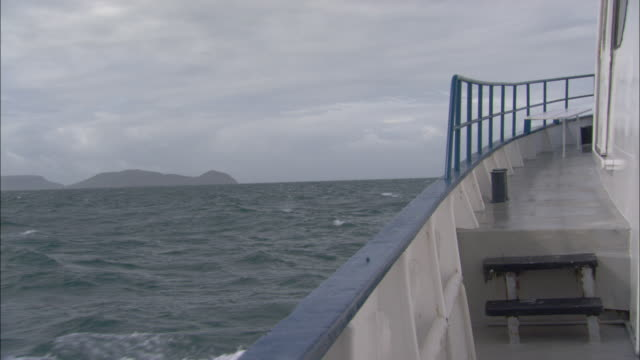 a powerboat sails in choppy seas along the great barrier reef. - railings stock-videos und b-roll-filmmaterial