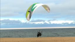 Powered Paragliders Flying Extremely Low Over Sandy Sea Beach