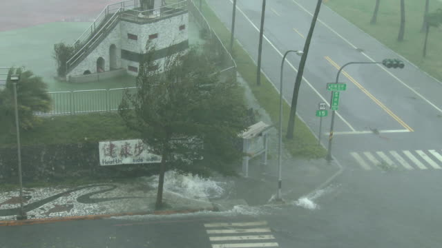 powerful eye wall wind and flooding rain lashes hualien city in taiwan as typhoon megi makes landfall on 27th september 2016 - メギ点の映像素材/bロール