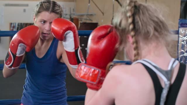 Powerful female boxer hitting her opponent