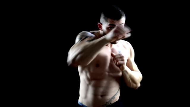 powerful shirtless and handsome male boxer punching on black background - shirtless stock videos & royalty-free footage