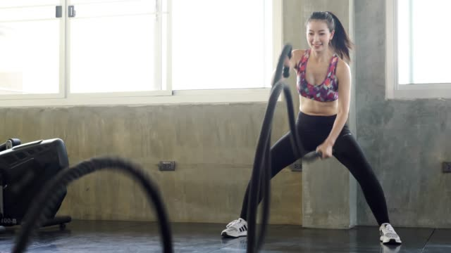 powerful sporty doing exercise battle rope indoor at fitness gym. woman taking weight loss with machine aerobic for slim and firm health. healthy sport cardio strong. - corda video stock e b–roll