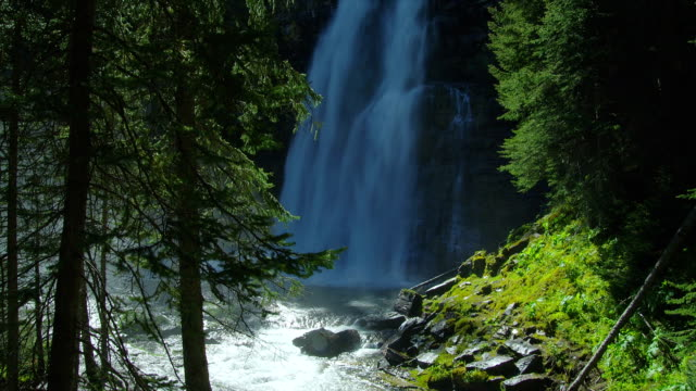 A powerful waterfall becomes a rushing river in Glacier National Park.