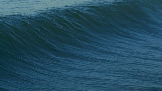vídeos de stock, filmes e b-roll de a powerful wave crashes at the beach and turns into whitewash. - slow motion - onda