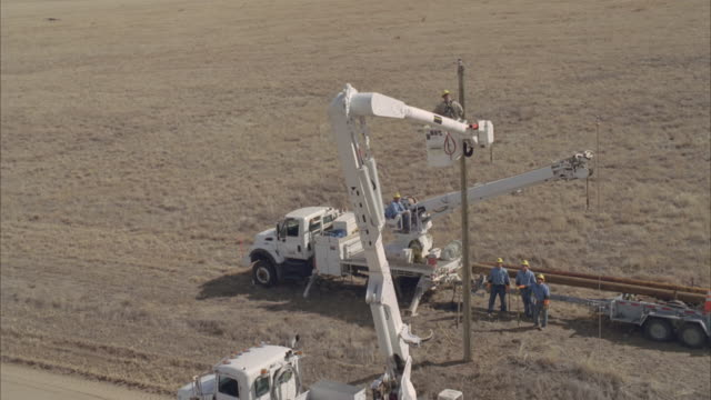 aerial powerline pole being adjusted to fit into ground / hooker, ok, usa - 発電所関係の職業点の映像素材/bロール