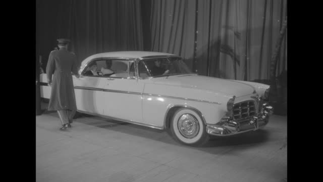 models on stage in evening dress stand walk in front of chrysler imperial and then a man approaches and stops the shot/ ws car on stage and doorman... - wrap dress stock videos and b-roll footage