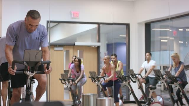 vídeos de stock, filmes e b-roll de praticar ciclismo indoor em uma aula de fitness - boa postura