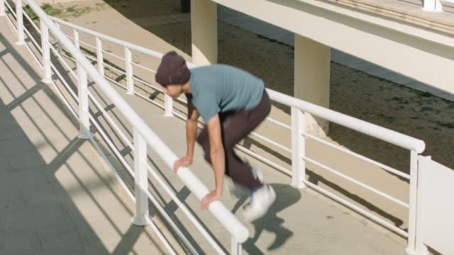 vídeos de stock, filmes e b-roll de praticando parkour na cidade - cerca