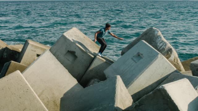 vidéos et rushes de pratiquant parkour dans le mer mur - danger