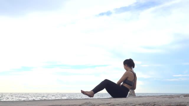 日没時にビーチでヨガを練習する - 地形点の映像素材/bロール
