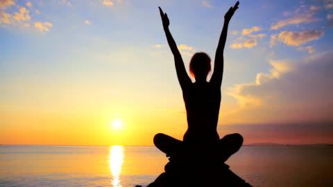 vídeos y material grabado en eventos de stock de dolly hd: practicar yoga en la playa al atardecer - yoga