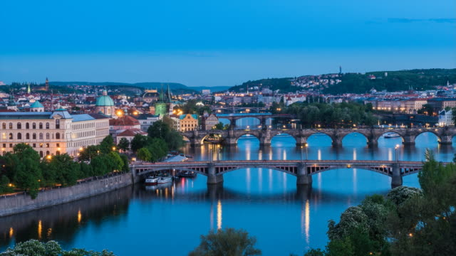 prague day to night time lapse, high angle long shot of old town and bridges over vlatava river - prague stock videos and b-roll footage