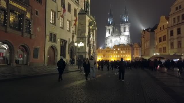 stockvideo's en b-roll-footage met praag toeristen wandelen in het oude stadsplein 's nachts - stare mesto