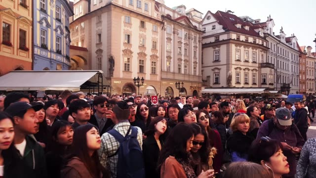 prague tourists watching the astronomical clock - astronomical clock prague stock videos and b-roll footage